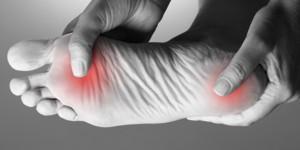 Bild einer Person, die ihren Fuß hält, wobei zwei rote Punkte Schmerz anzeigen