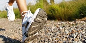 Bild der Füße eines Läufers auf einem Kiesweg
