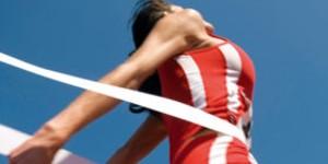 Bild einer Frau, die ein Fußrennen gewinnt und das Ziellinienband bricht